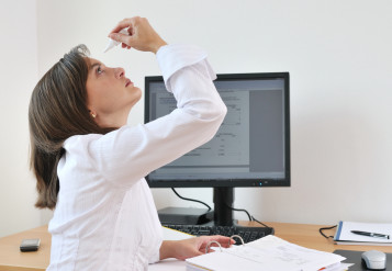 female office worker sitting at a computer takes a break to apply eye drops