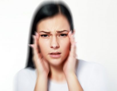 blurred image of a female holding her temples and struggling to see clearly
