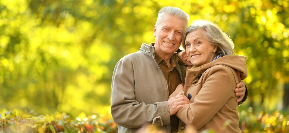 older couple smiling and embracing while outdoors in the Fall