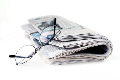 pair of reading glasses resting on a closed newspaper - white background