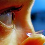 close up of someone placing a contact lens in their right eye