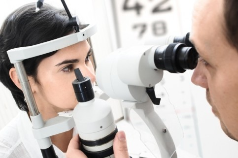 a young female patient at the optician having her vision tested
