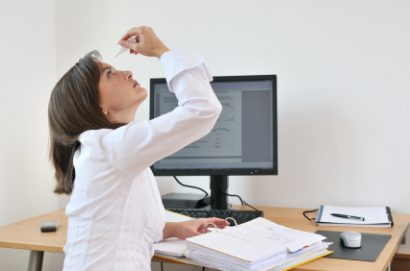 female office worker taking a break from working on her computer to apply eye drops