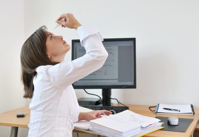 female office worker takes a break from her computer to apply eye drops