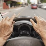 POV close up of an older driver with their hands on the wheel, looking out the windshield at the road