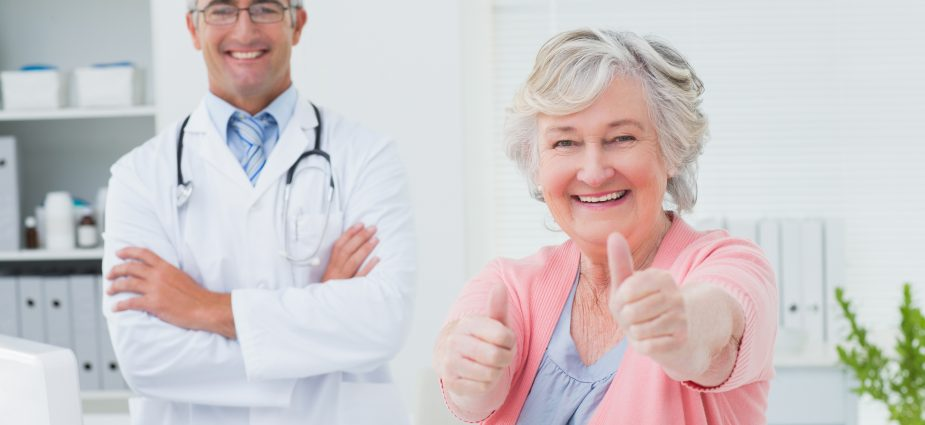 older female vision patient sitting next to her doctor and giving thumbs up