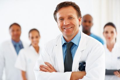 smiling male doctor in white lab coat smiling with a team of doctors behind him