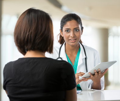 female doctor in a white lab coat speaking with a female patient about vision treatment
