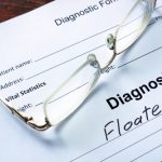 reading glasses sitting on top of a worksheet showing a diagnosis of eye floaters
