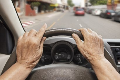 POV of an older, female driver with her hands on the steering wheel staring through the windshield