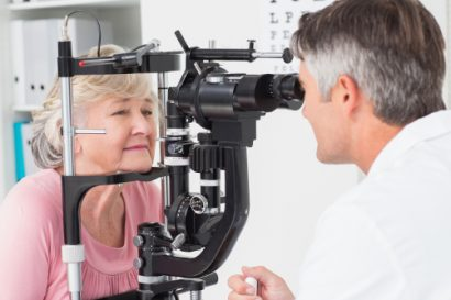 older female eye surgery patient undergoing a comprehensive exam