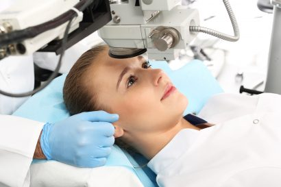 female patient laying down to have her eye examined as part of treatment