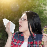 Woman with Seasonal Eye Allergies getting ready to sneeze into a tissue