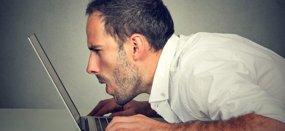 man with his face extremely close to his laptop screen
