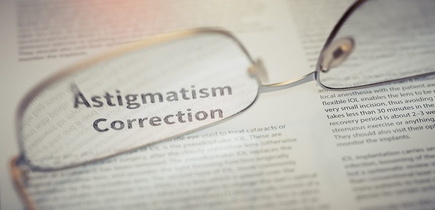 reading glasses sitting on a newspaper and highlighting astigmatism correction