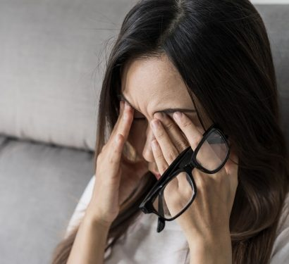 tired woman with glasses rubbing her eyes on sofa